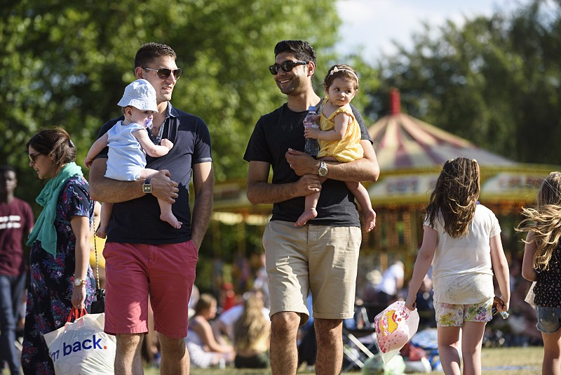 Dads holding young children at Party in the Park