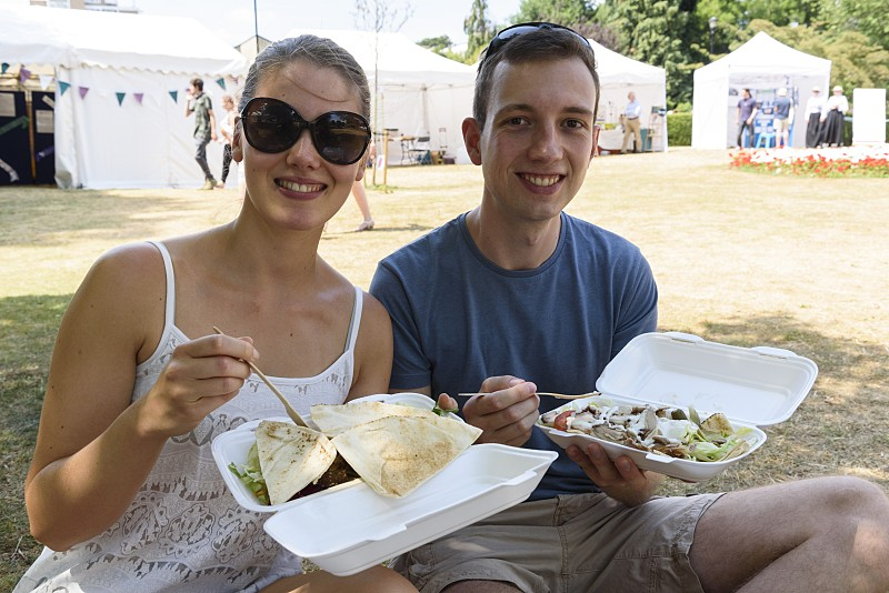 A couple enjoying hot food from the food village
